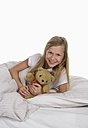 Girl lying on bed with teddy bear, smiling - WWF001874