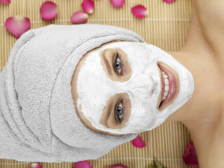 Young woman with face mask at spa, smiling, portrait - JLF000353