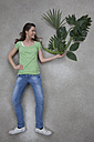 Mid adult woman holding plant, smiling - BAEF000213