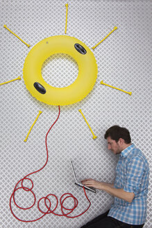 Mid adult man using laptop connected to sun shape float - BAEF000228