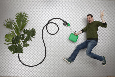 Mid adult man holding petrol can and hose connected to plant - BAEF000231