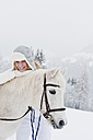 Austria, Salzburg, Hüttau, Young woman with white horse, smiling, portrait - HHF003619