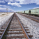 USA, Empty railway track and freight train passing - WBF000985