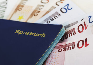 Close up of bank book on fanned euro notes - WBF001022