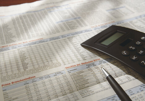 Close up of calculator on newspaper with share prices - WBF001034