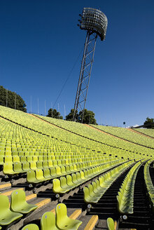 Germany, Bavaria, Munich, View of green seats with floodlights in olympic stadium - PS000432