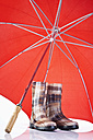 Close-up of rubber boots and umbrella - MAEF003196