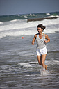 Greece, Crete, Mature woman running in water - AKF000335