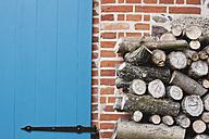 Germany, Kratzeburg, Stack of firewood near country house - WESTF016581