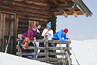 Italy, Trentino-Alto Adige, Alto Adige, Bolzano, Seiser Alm, People standing outside ski resort near railings - MIRF000117