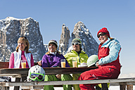 Italy, Trentino-Alto Adige, Alto Adige, Bolzano, Seiser Alm, People sitting on bench with skiing equipment and drinks - MIRF000120