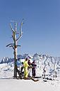 Italy, Trentino-Alto Adige, Alto Adige, Bolzano, Seiser Alm, People resting near bare tree on snowy landscape - MIRF000123