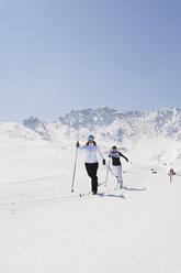 Italy, Trentino-Alto Adige, Alto Adige, Bolzano, Seiser Alm, Two women doing cross-country skiing - MIRF000168