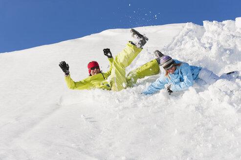 Italy, Trentino-Alto Adige, Alto Adige, Bolzano, Seiser Alm, Man and woman jumping on snow - MIRF000186