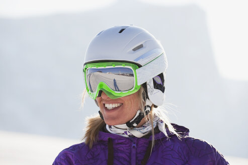 Italy, Trentino-Alto Adige, Alto Adige, Bolzano, Seiser Alm, Young woman wearing skiing helmet and ski goggles, smiling, close up - MIRF000192