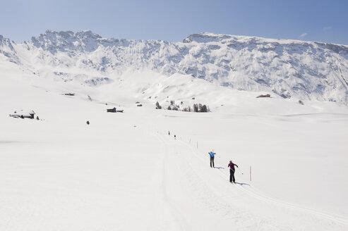 Italy, Trentino-Alto Adige, Alto Adige, Bolzano, Seiser Alm, Man and woman doing cross-country skiing - MIRF000198