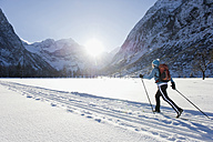 Germany, Bavaria, Senior woman doing cross-country skiing with karwendal mountains in background - MIRF000213