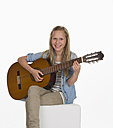 Girl playing guitar against white background, smiling, portrait - WWF001898