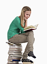 Girl sitting and reading on stack of books against white background - WWF001905