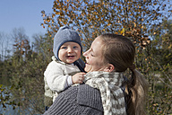 Gemany, Bavaria, Munich, Mother holding baby boy, smiling, looking at camera - RBF000689
