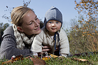 Gemany, Bavaria, Munich, Mother with baby boy lying on grass, close up - RBF000692