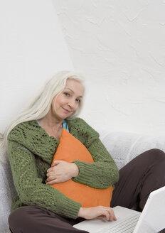 Germany, Duesseldorf, Woman hugging cushion besides laptop on sofa - UKF000205