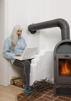 Germany, Duesseldorf, Woman using laptop near fireplace - UKF000209