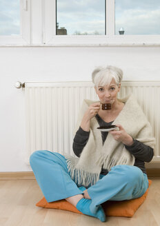 Germany, Duesseldorf, Woman drinking tea near heater at home, smiling, portrait - UKF000217