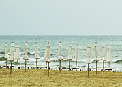 Spain, Alicante, View of empty beach with tied beach umbrellas and sun loungers - MBEF000087