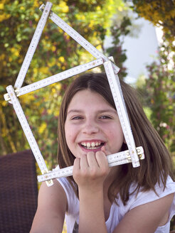 Close up of girl holding house shape made up of folding ruler, smiling, portrait - LFF000230