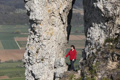 Germany, Bavaria, Franconia, Franconian Switzerland, Walberla, View of mature woman hiking near rock formations on mountain - SIEF001407