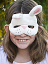 Germany, Bavaria, Close up of girl wearing easter bunny mask, smiling, portrait - LFF000256