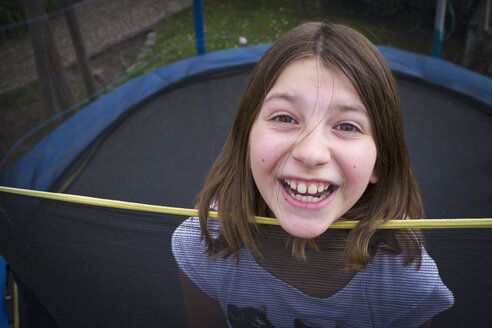 Germany, Bavaria, Girl jumping on trampoline, smiling, portrait - LFF000259