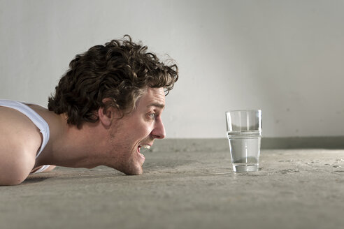 Mid adult man lying on floor and staring at glass of water - DBF000093