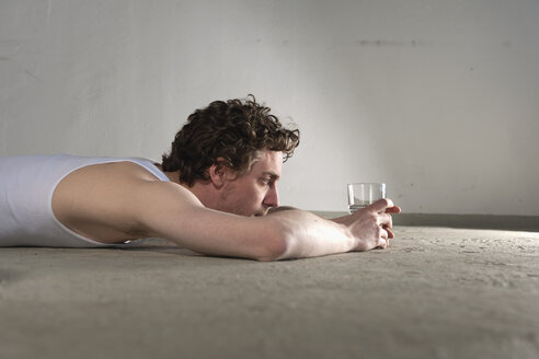 Mid adult man lying on floor and staring at glass of water - DBF000095