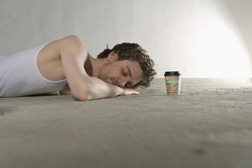 Mid adult man lying on floor with coffee cup beside - DBF000096