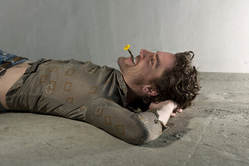 Mid adult man lying on floor and holding flower in mouth - DBF000099