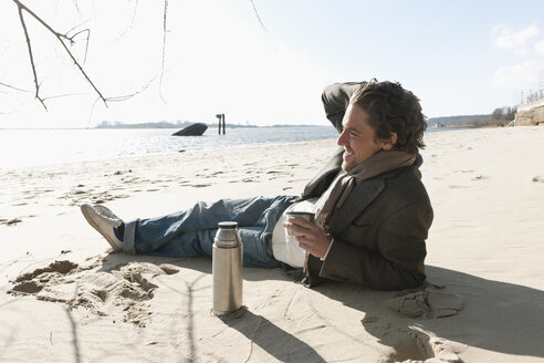 Germany, Hamburg, Man lying on sand with coffee flask near Elbe riverside - DBF000101