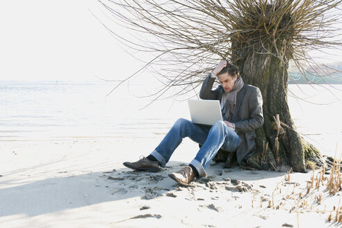 Germany, Hamburg, Man sitting beside tree and using laptop near Elbe riverside - DBF000082