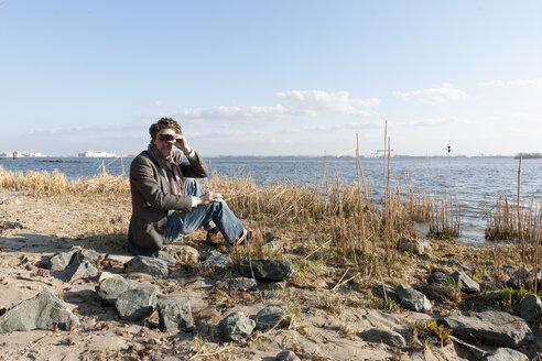 Germany, Hamburg, Man looking through binoculars near Elbe riverside - DBF000126