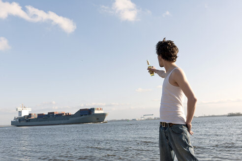 Germany, Hamburg, Man with beer bottle near Elbe riverside and container ship in background - DBF000130