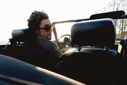 Germany, Hamburg, Man driving classic cabriolet car - DBF000140