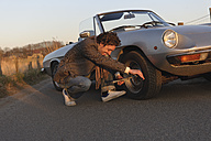 Germany, Hamburg, Man changing tyre of classic cabriolet car - DBF000111