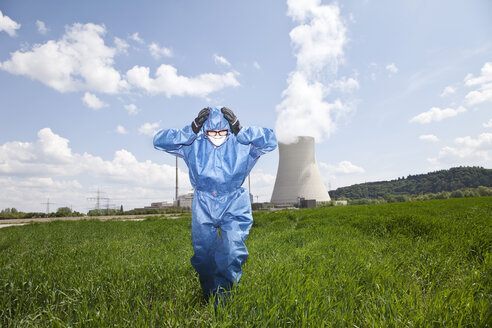 Germany, Bavaria, Unterahrain, Man with protective workwear walking in field at AKW Isar - MAEF003266