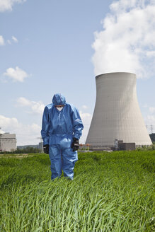 Germany, Bavaria, Unterahrain, Man with protective workwear standing and looking down in field at AKW Isar - MAEF003269
