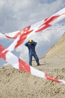 Germany, Bavaria, Man in protective wear on sand dune and cordon tape in foreground - MAEF003304
