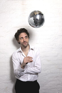Mid adult man looking at disco ball - DBF000064