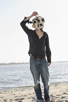 Germany, Hamburg, Mid adult man covering his face with torn football near Elbe river - DBF000074