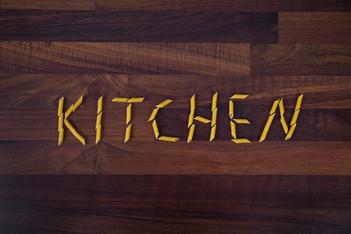 Close up of word kitchen written with penne on wooden background - TSF000257