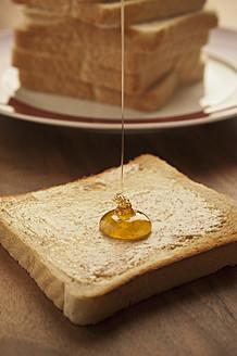Germany, North Rhine-Westphalia, Düsseldorf, Close up of honey falling on toast - KJF000098